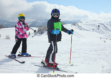 skiing kids - two children are standing on ski mountain
