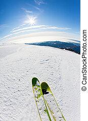 Skiing on a ski slope: closeup perspective, fish-eye lens,...