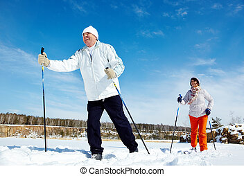 Skiing people - Portrait of mature couple skiing outside