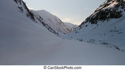 Skiing in the Alps, down a valley in late afternoon twilight
