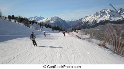 Skiing in the alps, first person point of view sliding down the snowy slope