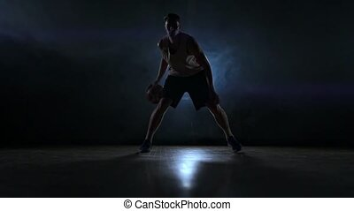 Skill dribbling basketball player in the dark on the basketball court with backlit back in the smoke. Slow motion streetball