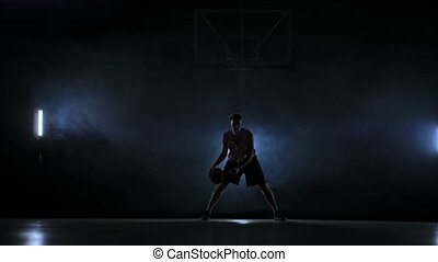 Skill dribbling basketball player in the dark on the...