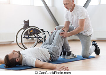 Skilled aged orthopedist stretching the disabled person in the gym
