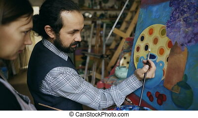 Skilled artist man teaching young girl to draw paintings and explaining the basics in art studio