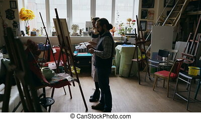 Skilled artist man teaching young girl to draw paintings and explaining the basics in art-class