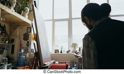 Skilled artist man teaching young woman painting on easel at art school studio - creativity, education and art people concept