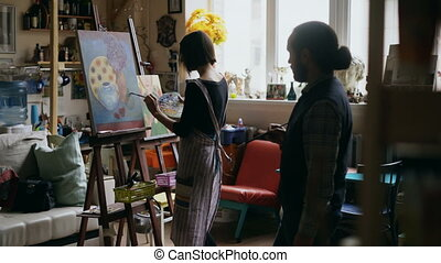 Skilled artist man teaching young woman painting on easel at...