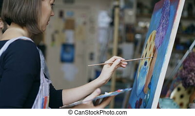 Skilled artist teacher showing and discussing basics of...