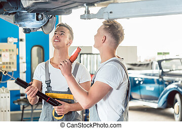 Skilled auto mechanic replacing the shock absorbers of a car