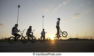 Skilled biker guy entertaining his friends doing rotation...