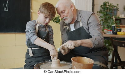 Skilled boy in dirty apron is molding vase in throwing wheel working with caring grandfather in workshop busy with creative activity. Hobby and children concept.