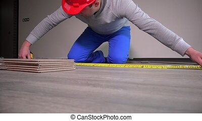 skilled builder with red hard hat lay laminate flooring at...