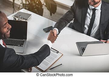 Skilled businessmen are shaking hands