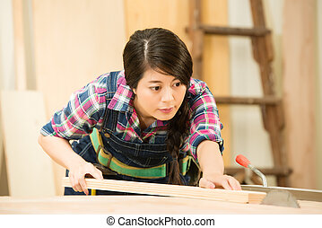 Skilled carpenter cutting a piece of wood in her woodwork...