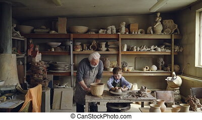 Skilled child is forming pot on potter's wheel while working...
