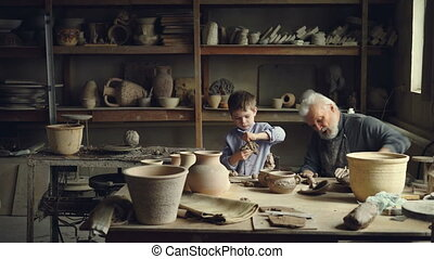 Skilled child is helping his senior grandfather professional...