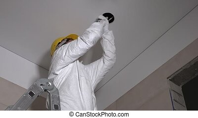 Skilled constructor man making plasterboard ceiling holes for light installation