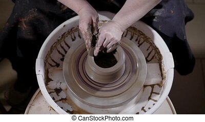 skilled craftsman is shaping and correcting clay cup on a...