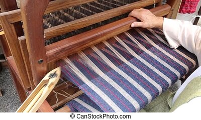 skilled craftsman weaves a fabric with an ancient hand loom...