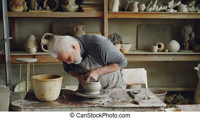 Skilled elderly potter is producing ceramic pot on turning...