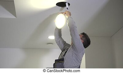 Skilled electrician man connect wires to led light panel and mount into ceiling