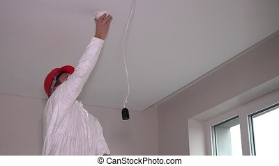 Skilled electrician man mount fire smoke alarm system on ceiling