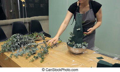 Skilled florist creates a flower arrangement with eucalyptus populus
