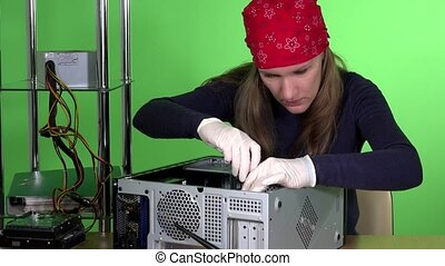 Skilled girl with headscarf repairing desktop pc. Computer...