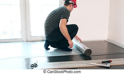 Skilled guy with red helmet lay sub-flooring mat in new apartment