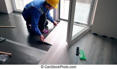 Skilled handyman guy with yellow hard hat installing laminate boards on floor