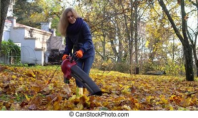Skilled landscaper woman blowing autumn leaves with leaf blower in customer house yard. Gimbal motion shot.