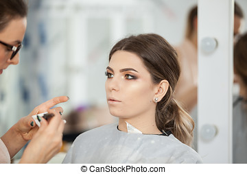 Skilled Makeup artist in working process. Applying make up...
