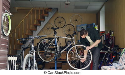Skilled male mechanic is fixing bicycle wheel with wrench...