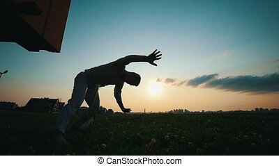 Skilled man dancing capoeira on the grass at sunset, the...