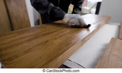 skilled man is vanishing wooden blanks inside a workshop,...