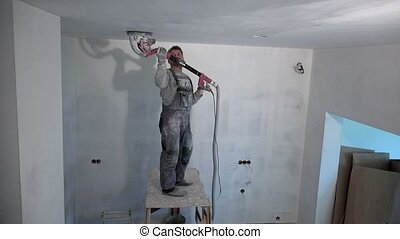 man standing on scaffolding polishing ceiling with grinder...