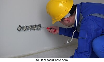 Skilled man with helmet testing wall socket with voltmeter....