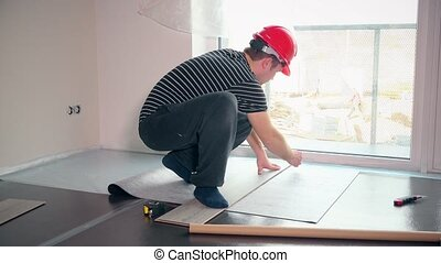 Skilled man with red helmet lay sub-flooring mat in new apartment