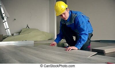 Skilled master builder laying wooden laminate boards on floor
