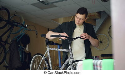 Skilled mechanic is fixing handle-bar of modern bicycle...