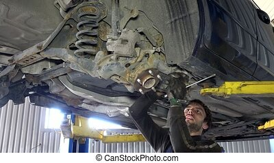 Skilled mechanic removing worn car parts in garage under automobile.