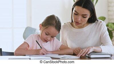 Skilled mother tutor teaching little kid girl writing. - ...