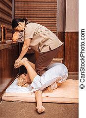 Skilled nice Asian masseuse doing Thai massage