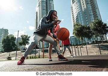 Positive joyful man running with a ball