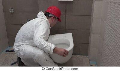 Skilled plumber man hanging heavy toilet bowl pan in new...