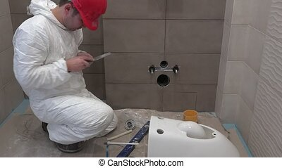 Skilled plumber man working on toilet bowl hand mount in new...
