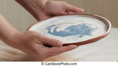 Skilled potter glaze covers the plate from red clay. Close...