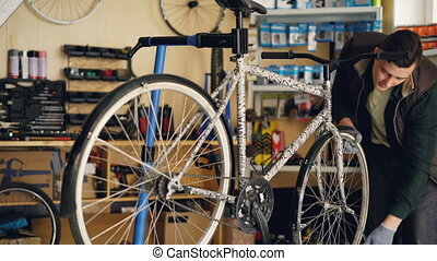 Skilled repairman is concentrated on repairing bicycle wheel fixing it with professional wrench while working in small workshop. Maintenance and people concept.