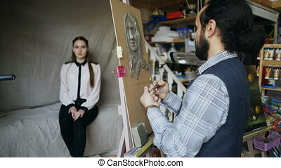 Skilled sculptor works with plasticine on canvas to create...